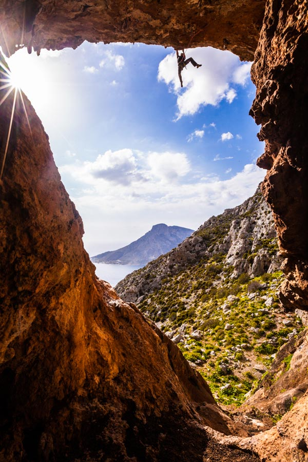 Person rock climbs and hangs from cliff in Kalymnos, Greece