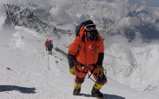 Chris Bombardier approaches top of everest in Mountainsmith backpack