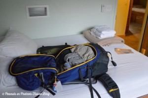 The Mountainsmith Lariat 65 with its giant U zipper lies on a bed