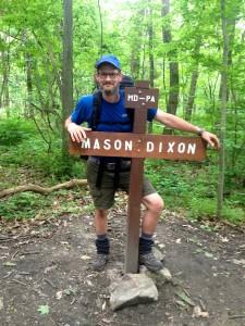 Appalachian trail thru hiker Slim Jim aka Chris Spencer crosses the Mason Dixon line