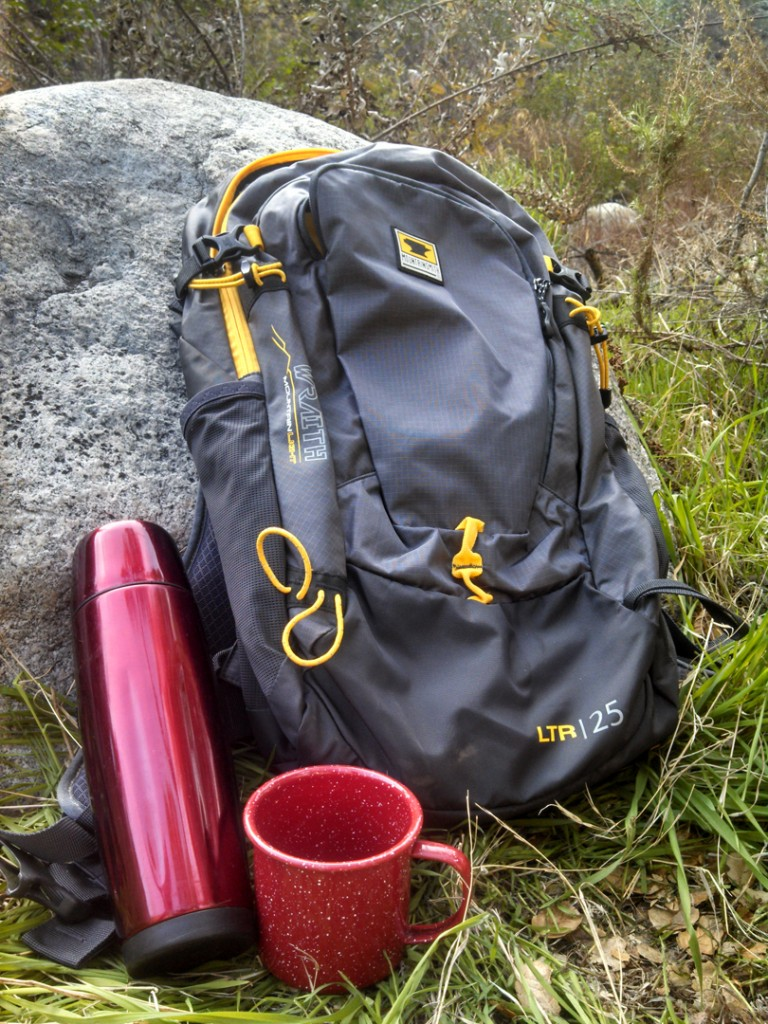A coffee urn and mug next to the Mountainsmith Wraith 25 backpack
