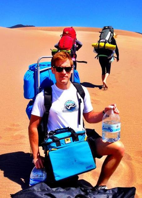 hiker carries the Mountainsmith deluxe cooler cube in Colorado's Sand Dunes