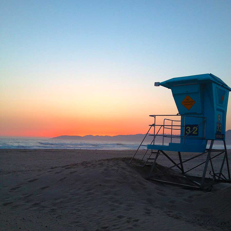 Sunset at Grover Beach, California. Blue lifeguard stand in the foreground, and a colorful sunset over the ocean in the background.