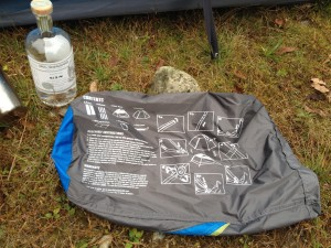The instructions of the Mountainsmith Genesee Tent appear on the side of the stuff sack next to a bottle of gin