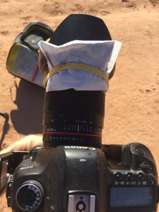 Hand warmer attached to camera lens with rubberband