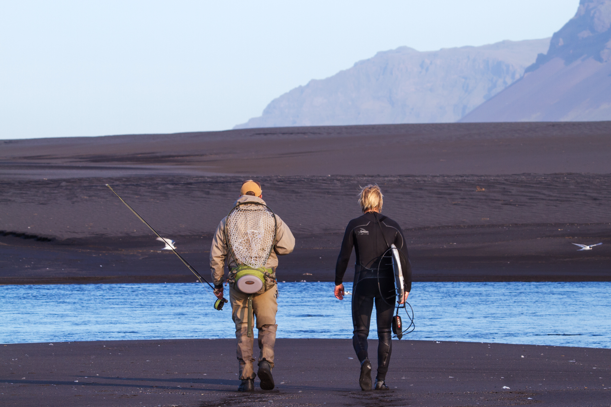 "a surfer and a fisherman walk along the beach in Iceland, from the movie ""YOW: Icelandic for Yes"""