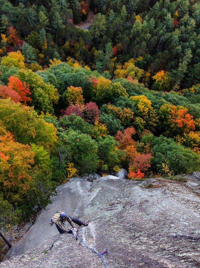 Climbing at Cathedral Ledge, New Hampshire with a colorful green and yellow background in the fall.