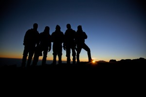 silhouettes of hikers standing at the summit of mt. kilimanjaro in tanzania