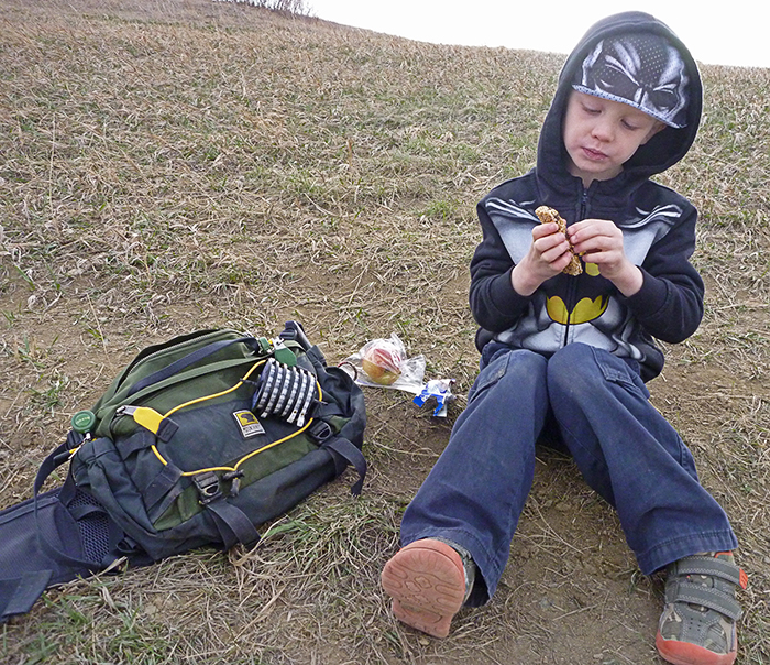 Kid snacking on the river bank in Denver, while on a fly fishing trip with his dad, sitting next to a Mountainsmith Tour TLS Lumbar Pack.