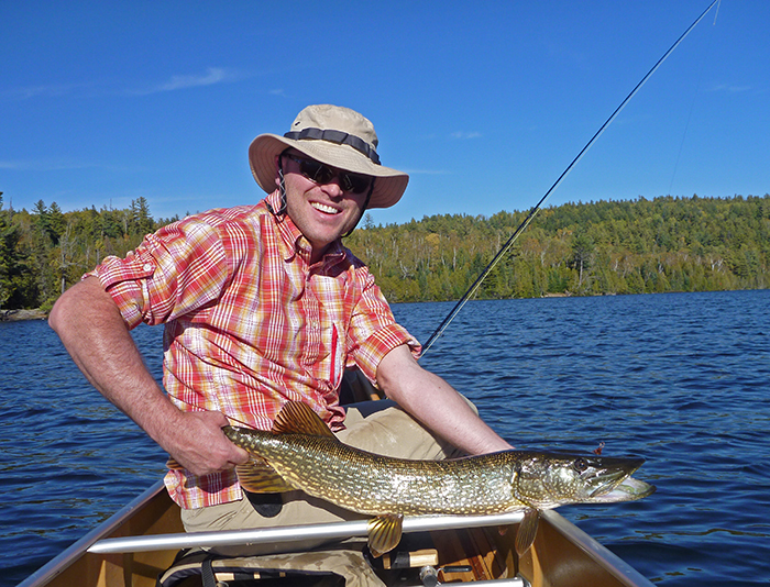 Jon Hill holding a fish in the Boundary Waters Canoe Area