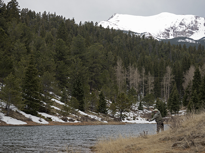 a fisherman casts a line near pikes peak