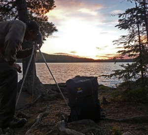 Randy Wilson taking a photo of the sunset with his Mountainsmith Spectrum camera backpack