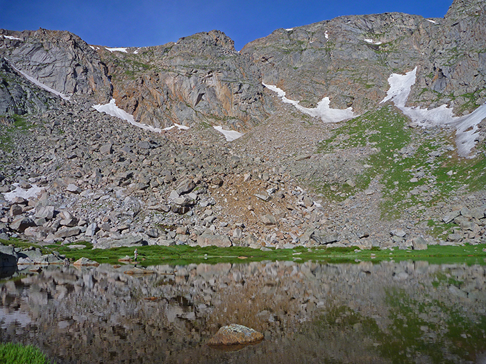 Blue sky day over an unnamed Colorado lake.  Mountainsmith Ambassador Jonathan Hill fly fishes in the distance.