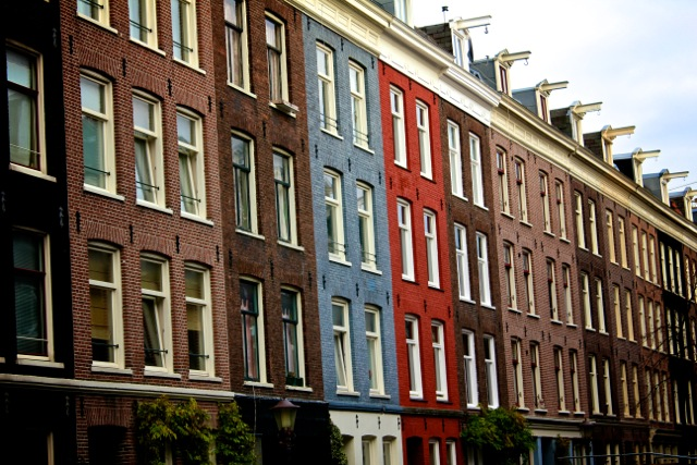 A red and blue house stick out in a row of houses in Amsterdam