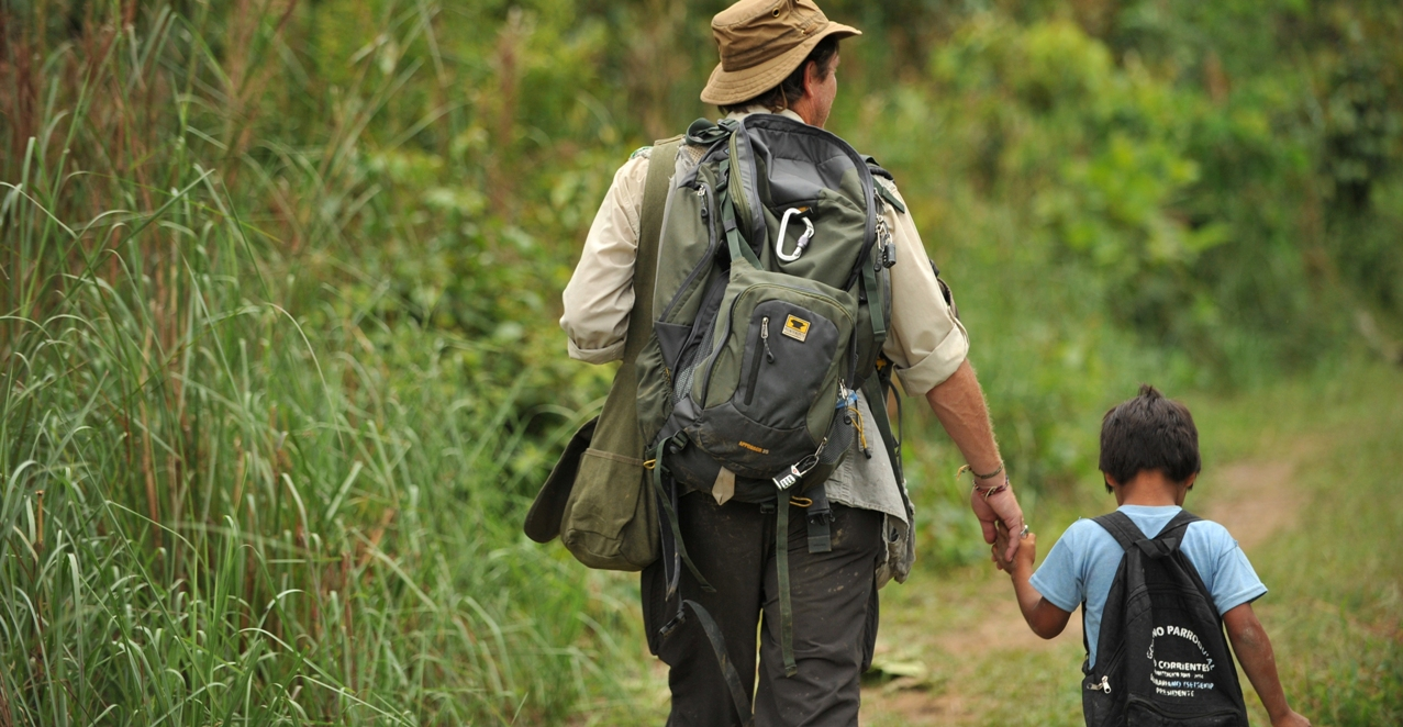 Dean Jacobs holds the hand of a little boy from the Achuar nation and carries his Mountainsmith Approach 35 backpack