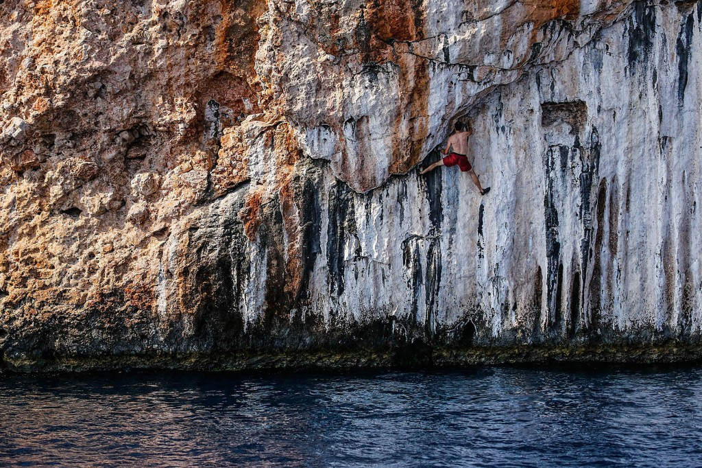 A climber is spread eagle while deepwater solo cimbing near olympos turkey