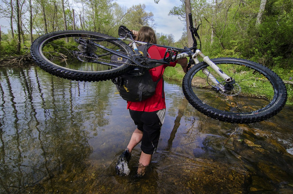 Curtis Savard wades through water with his mountian bike over his shoulder and a Mountainsmith Wraith 25 backpack on, image by aaron codling