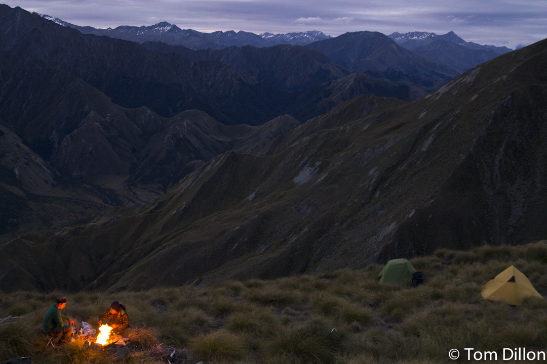 campfire and two tents in the mountains in new zealand