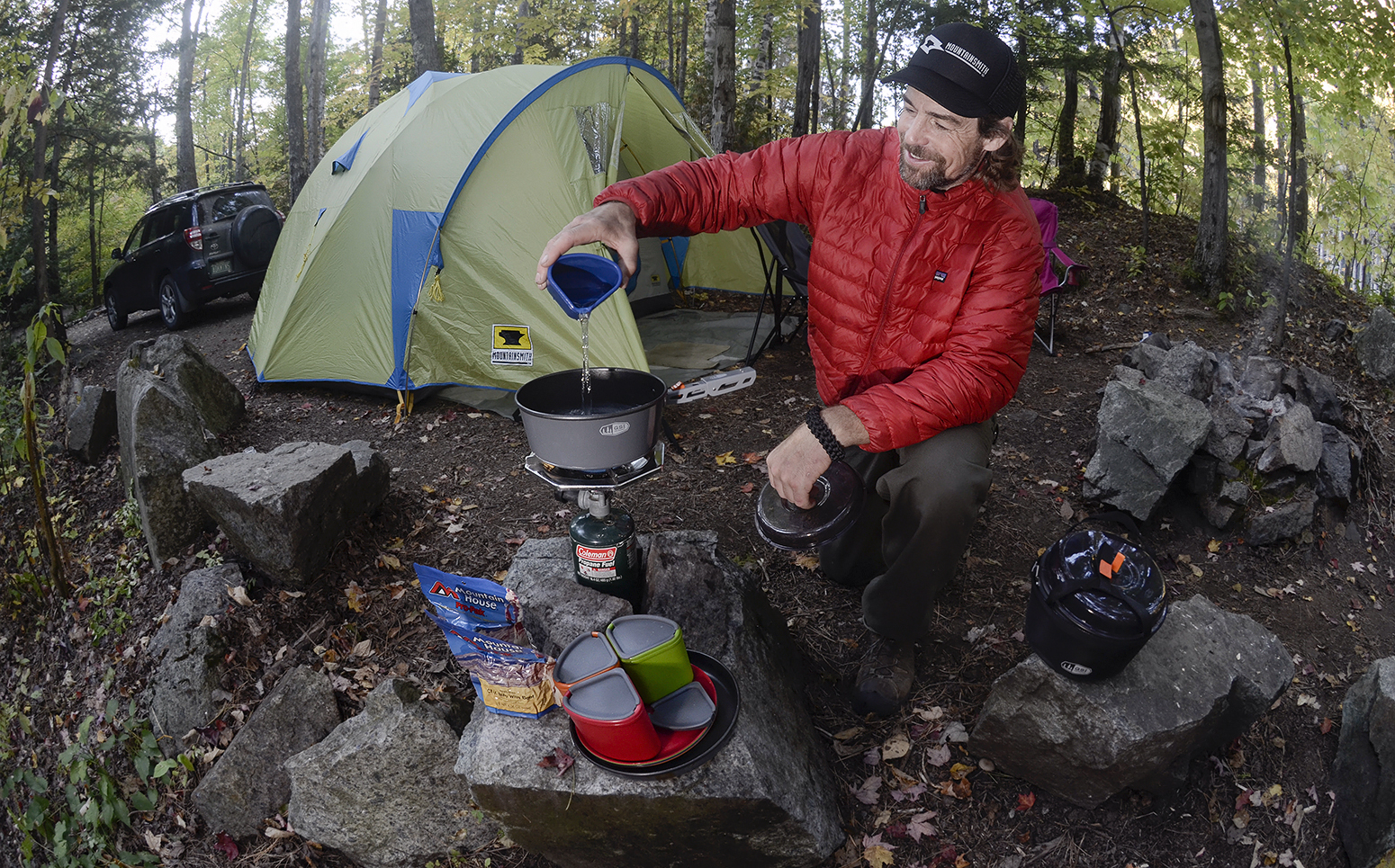 Curtis Savard prepares food at his campsite in front of the Mountainsmith Conifer tent