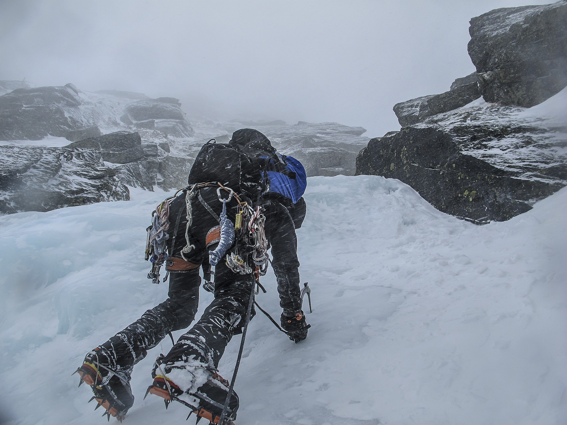 a mountaineer clings to ice with crampons and an ice ax, photo by Chris Vultaggio