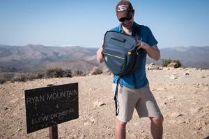 Man reaching into Mountainsmith camera bag while hiking
