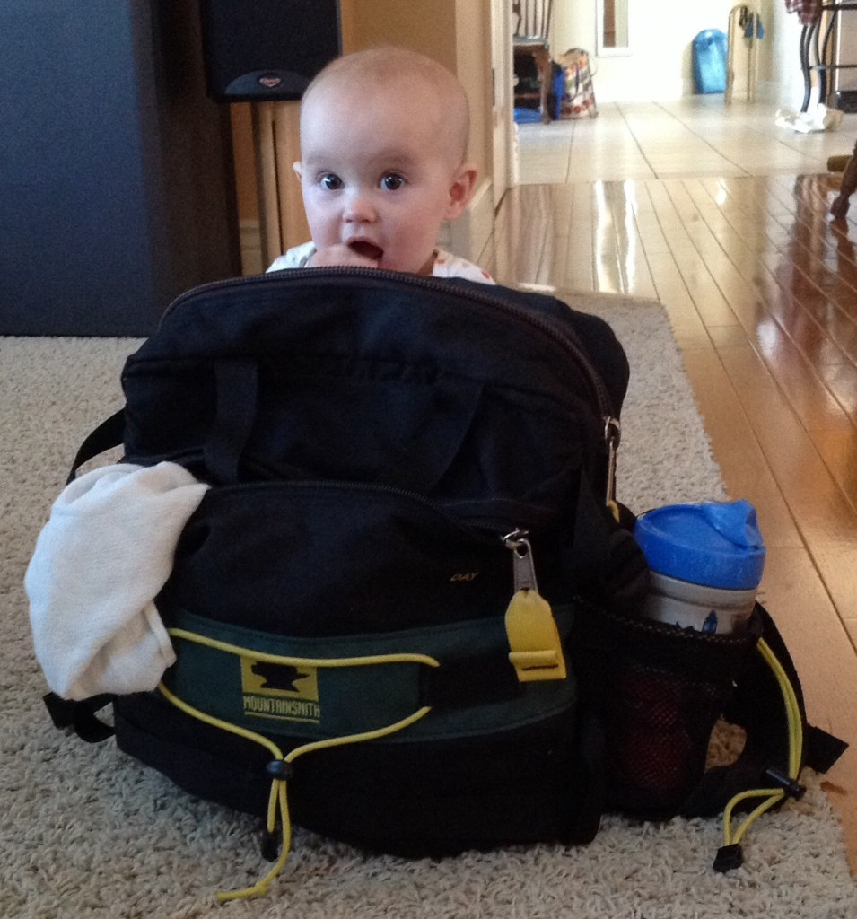 a baby sits behind a Mountainsmith Day pack being used for a diaper bag