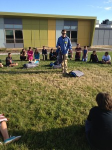 Jeremy Dodge presents to the Denver Green School students on the soccer field, setting up the Conifer 5+ tent