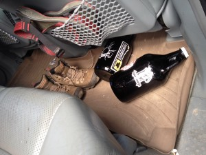 Two growlers, one from Cannonball Creek and one from Golden City Brewery with an UpaDowna sticker roll around the back seat of a car