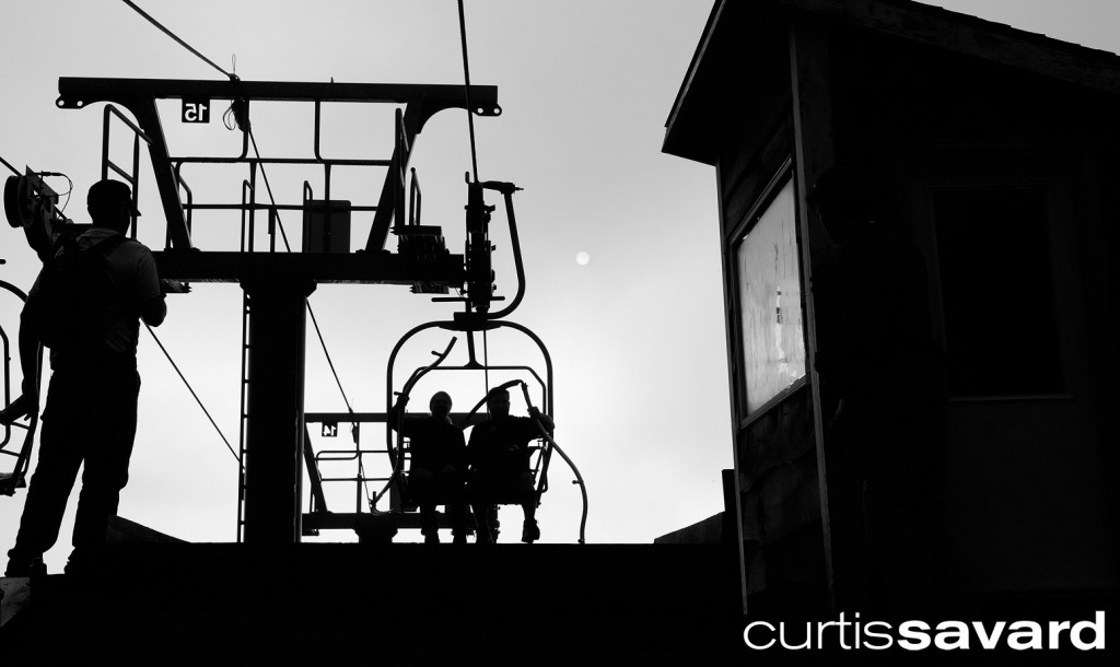 silhouette of two mow crew workers riding the mad river glen double chair